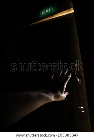 Hand of a man trying to open old door and escape from the dark into the light - stock photo