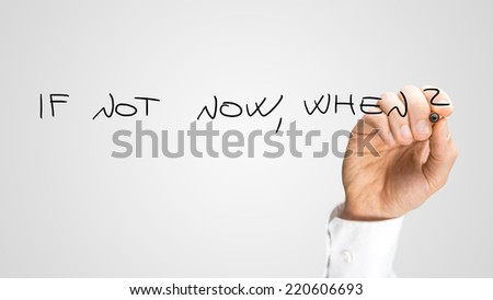 Hand of a man writing a rhetorical question on a blank virtual interface - If Not Now, When - demanding an answer in the face of procrastination, with copyspace - stock photo