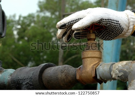 hand of a miner turned oil taps - stock photo