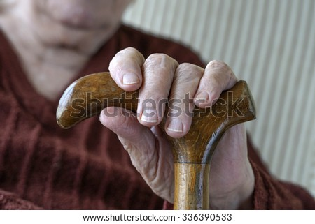 hand of a senior person holding wooden cane - stock photo