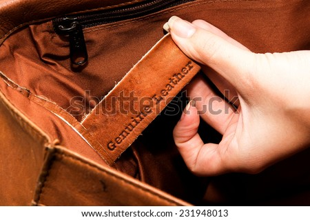 Hand of a woman holding a genuine leather label - stock photo