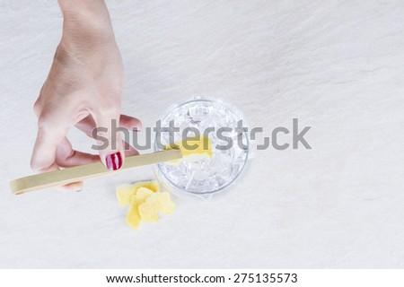 hand of a woman holding a lemon peel with  a bamboo ice tongs on a flavoring process of a gin tonic on a gin tonic preparation session - focus on the lemon peel - stock photo
