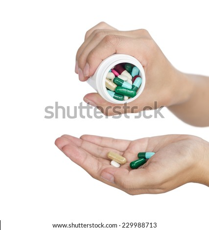 Hand of a woman holding a pill against white background. - stock photo