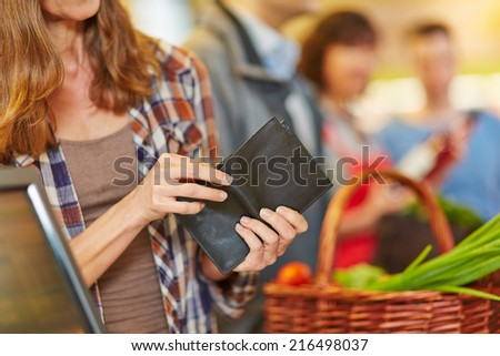 Hand of a woman looking for money in wallet at supermarket checkout - stock photo