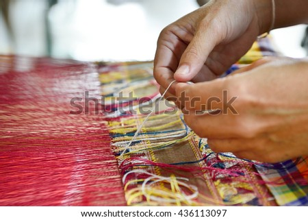 Hand of a woman weaving traditional silk fabric in Thailand - stock photo
