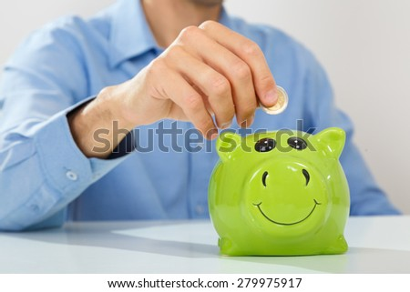 Hand of a young caucasian man putting coin into piggy bank - stock photo