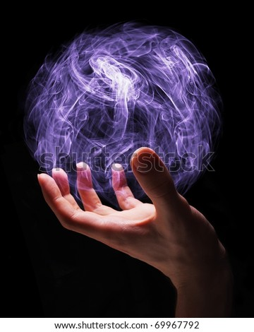 Hand of a young wizard creating a magical sphere. - stock photo