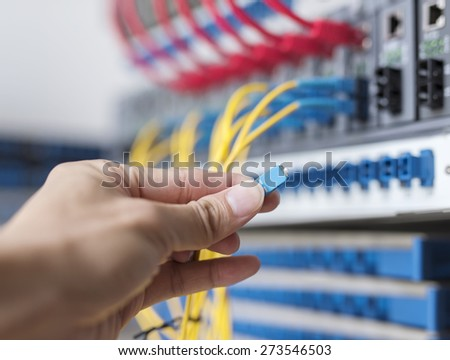 hand of administrator holding optic fiber cables with connectors - stock photo