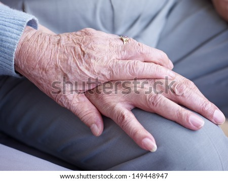 hand of an elderly woman holding the hand of an elderly man. - stock photo