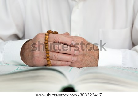 Hand of an old mullah holding rosary beads - stock photo