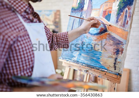 Hand of artist painting Italian landscape - stock photo