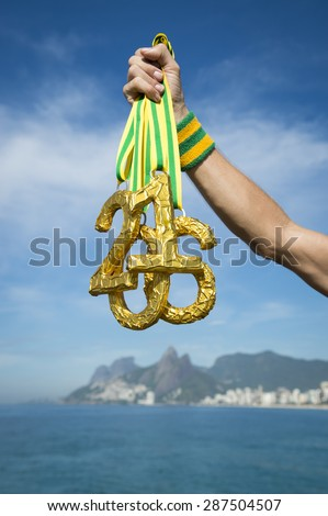 Hand of athlete holding 2016 gold medals outdoors on Ipanema Beach Rio de Janeiro Brazil  - stock photo