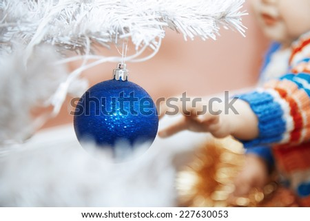 Hand of baby touching Christmas toy. Horizontal photo - stock photo