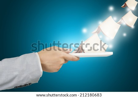 Hand of Business Man hold tablet using Old Book Data as E-book concept - stock photo