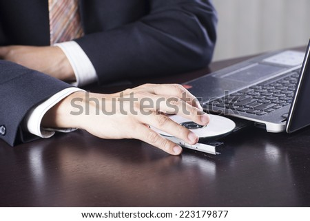 Hand of Business man insert disk to laptop computer  - stock photo