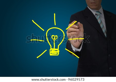 Hand of business man write a light bulb on tablet pc touch screen - stock photo