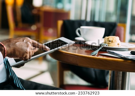 Hand of businessman using digital tablet while having breakfast in the cafe - stock photo