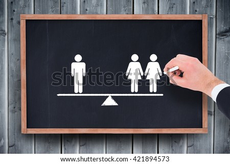 Hand of businessman writing with a white chalk against blackboard with copy space on wooden board - stock photo