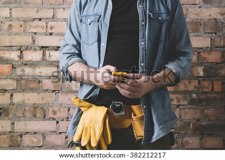 hand of carpenter with cell-phone - stock photo