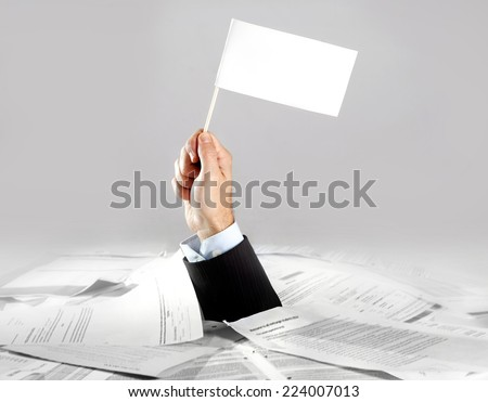 Hand of caucasian businessman emerging from office desk loaded of paperwork , invoices and a lot of papers and documents holding white flag  overworked in giving up concept - stock photo