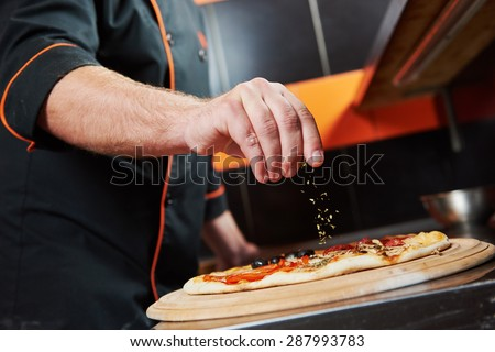hand of chef baker in uniform adding spice into pizza after pizza preparation at restaurant kitchen - stock photo