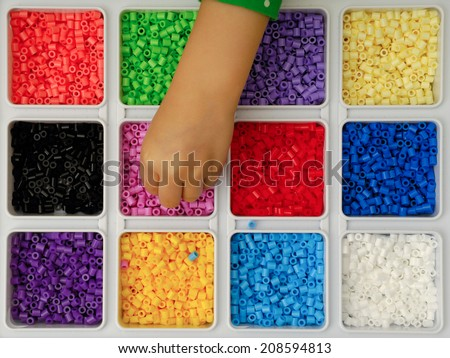 Hand of child is playing with toy pearls - stock photo
