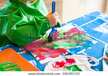 Hand of child painting with roller - stock photo