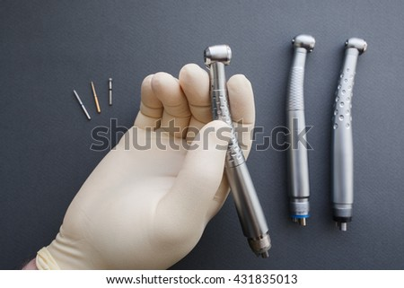 Hand of dentist in latex protective gloves holding dental drill handpiece. Flat lay of dental handpiece in dentist hand on gray background. Dental handpieces and bur tools on background - stock photo