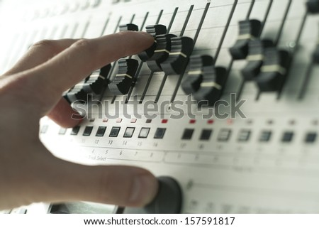hand of DJ tweaking knobs and moving sliders on mixer, modern way of creating music - stock photo