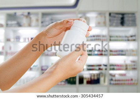 hand of doctor holding medicine bottle on medicine cabinet and store medicine and pharmacy drugstore - stock photo