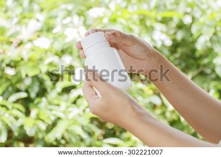 hand of doctor holding medicine bottle on nature background - stock photo