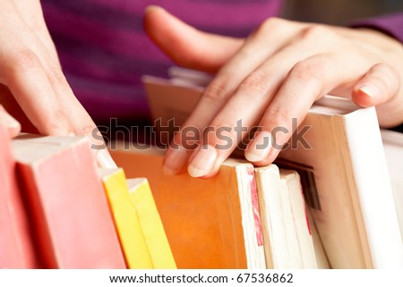 Hand of female looking for book in library - stock photo