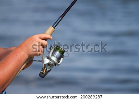 Hand of Fisherman`s  holding fishing rod over the blue water - stock photo