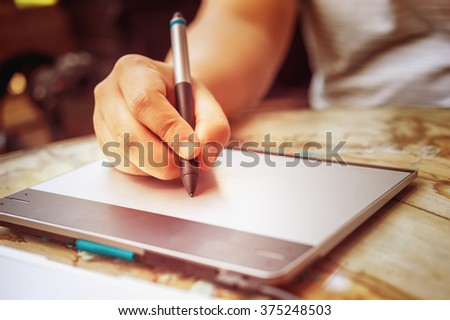 hand of Graphic Designer working with interactive pen display, digital Drawing tablet and Pen on a computer. - stock photo