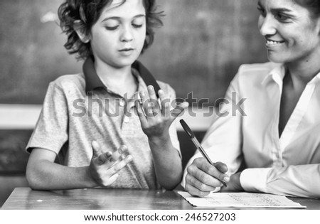 Hand of kid learning math with teacher. - stock photo