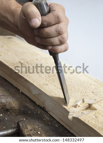 Hand of   man shaping wood with a gouge - stock photo