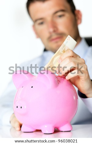 hand of man with bill and pink piggy bank - stock photo