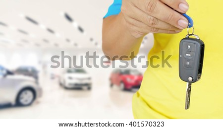 hand of man with car key on blur photo car showroom background - stock photo