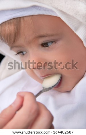 Hand of mother feeding nine month caucasian cute baby (boy) with a spoon. Happy little child (toddler) has healthy food. Close up.  - stock photo