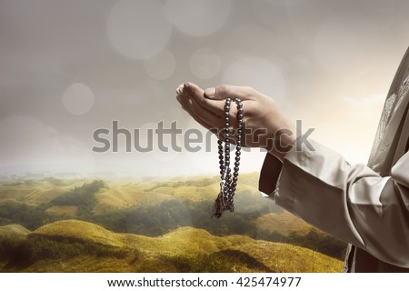 Hand of muslim people praying with hill landscape background - stock photo