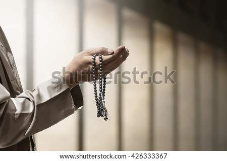Hand of muslim people praying with mosque interior background - stock photo