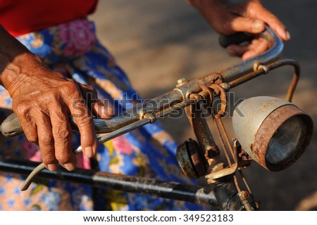 Hand of old people holding the bicycle handler with natural light effect - stock photo