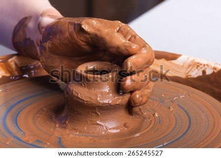 hand of potter with clay jug - stock photo