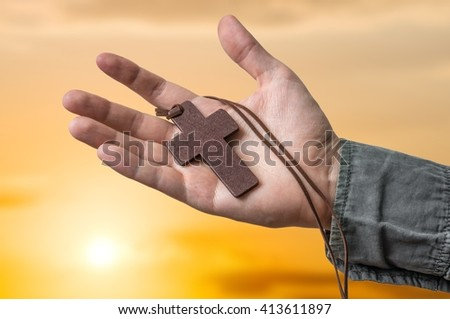 Hand of priest holding brown cross at sun set. - stock photo