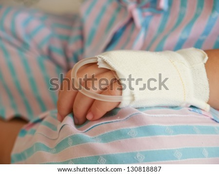 hand of sick Little girl in hospital bed - stock photo