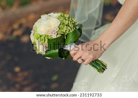 Hand of the bride with ring and wedding bouquet - stock photo