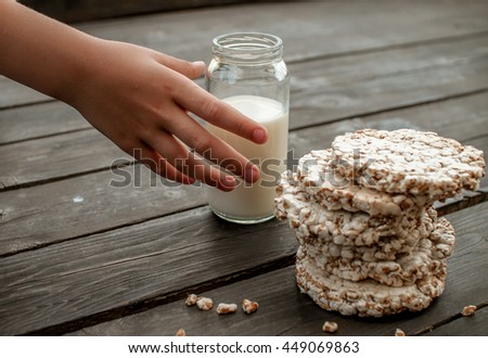 hand of the child takes home milk. tasty crispbread on wooden background table - stock photo