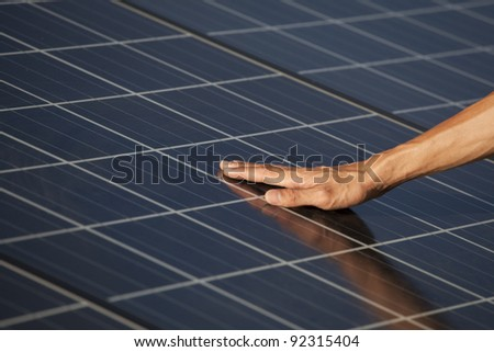 Hand of the man touching Solar cell. - stock photo