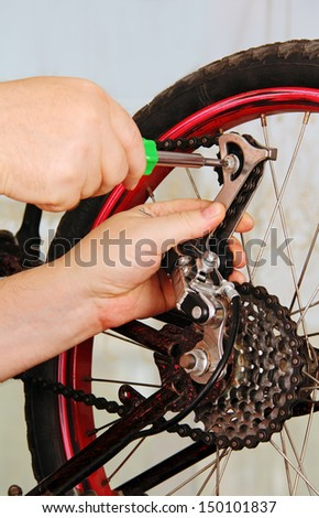 hand of the master with a wrench, repair a bicycle wheel. - stock photo