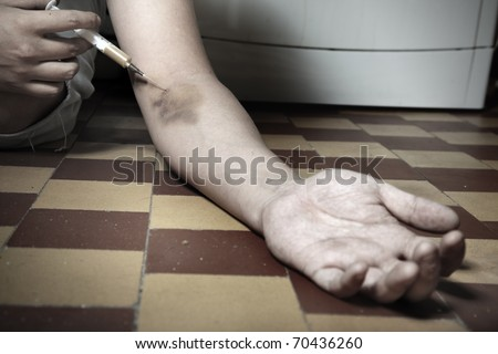 Hand of the narcotist with syringe on the floor. Artistic colors added - stock photo
